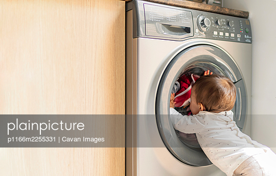 little girl looking at washing machine - p1166m2255331 by Cavan Images