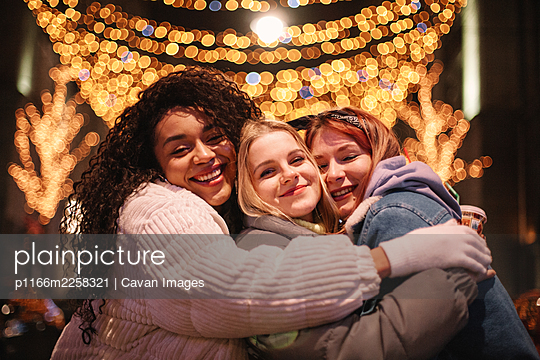 Happy female friends embracing standing by Christmas lights in city - p1166m2258321 by Cavan Images