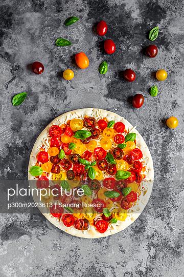 Unbaked pizza with tomatoes and basil leaves - p300m2023613 von Sandra Roesch
