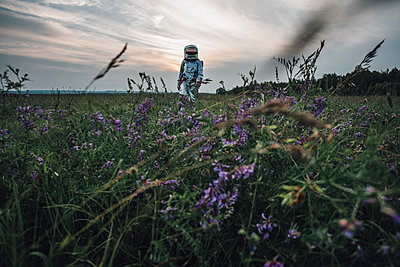 Spaceman exploring nature, standing in meadow, looking at sky - p300m2030546 by Vasily Pindyurin