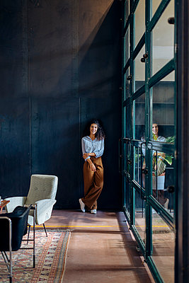 Portrait of young businesswoman standing at the window in loft office - p300m2144771 by Sofie Delauw