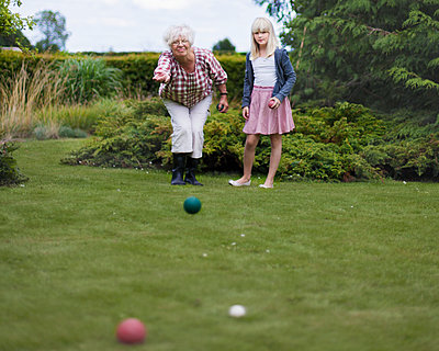 Grandmother and granddaughter playing petanque - p312m2200026 by Pernille Tofte