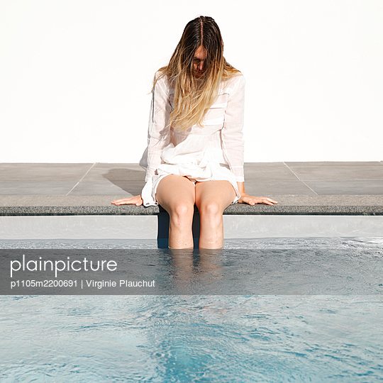 Young woman cooling her feet in the pool - p1105m2200691 by Virginie Plauchut