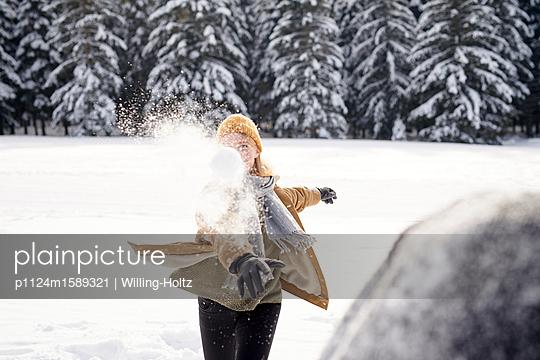 Junges Paar macht eine Schneeballschlacht - p1124m1589321 von Willing-Holtz