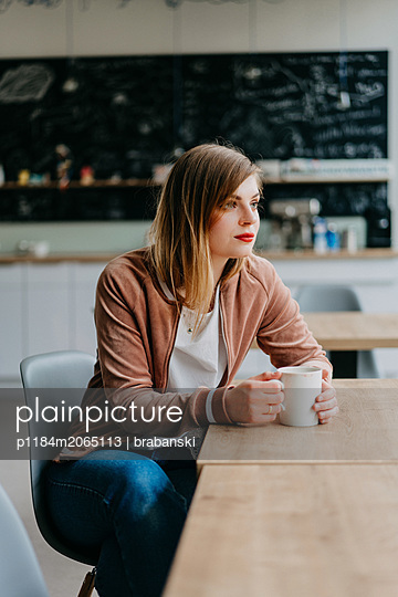 Woman sitting in a cafe - p1184m2065113 by brabanski