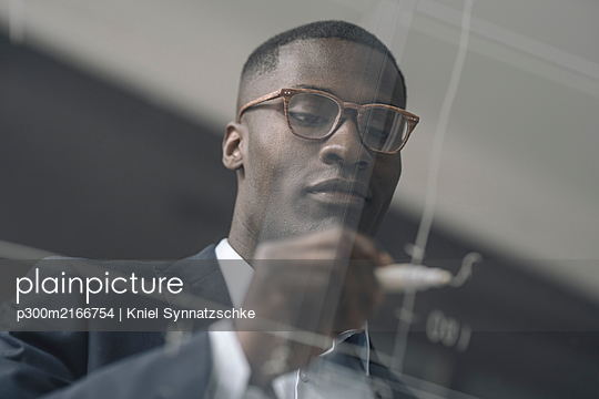 Portrait of young businessman drawing diagram on glass pane in office - p300m2166754 by Kniel Synnatzschke