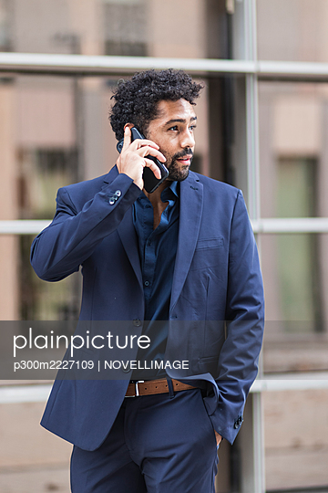 Entrepreneur talking on mobile phone while looking away in city - p300m2227109 by NOVELLIMAGE