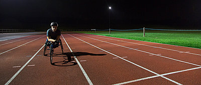 Portrait confident, determined young female paraplegic athlete training for wheelchair race on sports track at night - p1023m2067544 by Martin Barraud