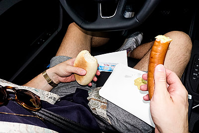 Man eating wiener in his car - p1301m2196929 by Delia Baum