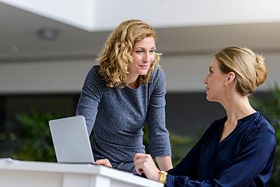 Two women talking at desk in office - p300m2154636 by Buero Monaco