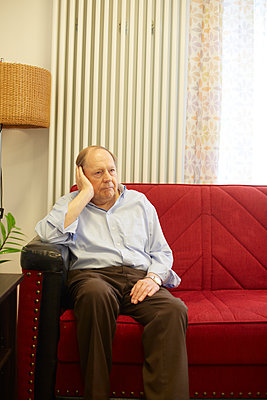 Age demented senior man sitting on couch in a nursing home - p300m2219181 by Heinz Linke