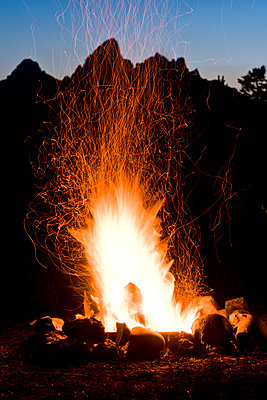 A campfire seen in front of mountains at dusk.  - p343m1184401 by Rob Hammer