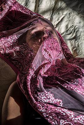 Junge Frau mit Schal über dem Gesicht auf einem Bett - p397m1556582 von Peter Glass