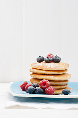 Berries and sugar on stack of pancakes - p42918000f by Tiina & Geir