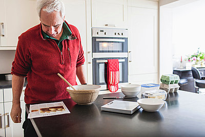 Senior male studying recipe on kitchen counter - p429m803069f by Hugh Whitaker