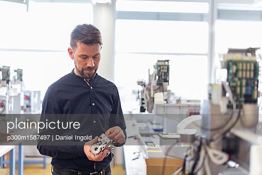 Man in factory examining product - p300m1587497 von Daniel Ingold