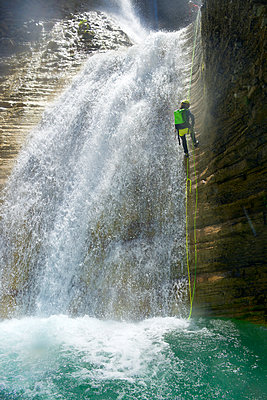Low angle view of female hiker rappelling on canyon amidst waterfall - p1166m2113029 by Cavan Images
