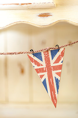 Triangular Union Jack before a traditional, rustic dresser. - p1433m1526052 by Wolf Kettler