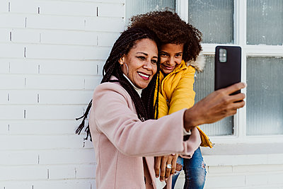Smiling mother taking selfie with daughter against wall - p300m2242570 by Eva Blanco