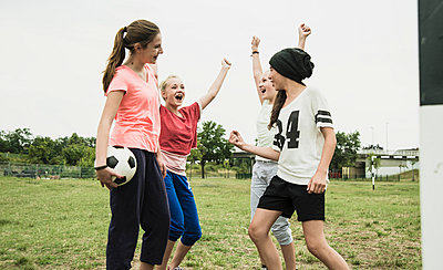 Four teenage girls having fun on a soccer field - p300m950159f by Uwe Umstätter