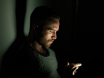 Young man using smartphone at night, face illuminated - p429m1052755 by Elke Meitzel