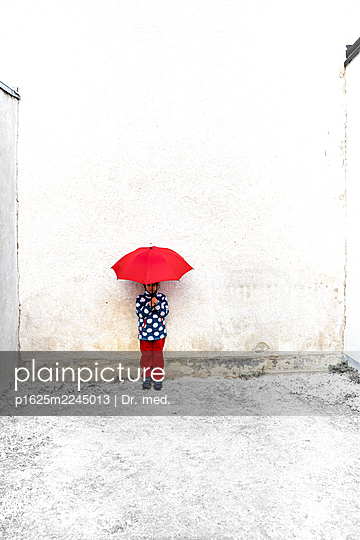 Little girl with red umbrella in a backyard - p1625m2245013 by Dr. med.
