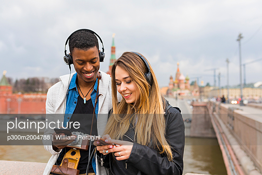 Russia, Moscow, multiracial best friends listening music with headphones - p300m2004788 von William Perugini