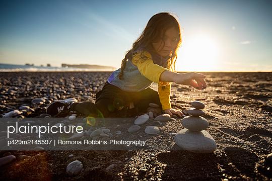 Little girl stacking wish stones, black sand beach, Reynisfjara, Iceland - p429m2145597 by Romona Robbins Photography