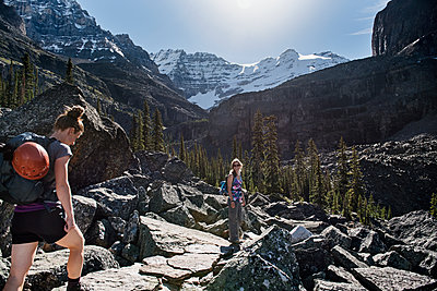 Women hiking in majestic, craggy mountain landscape, Yoho Park, British Columbia, Canada - p1023m2066474 by Jarusha Brown