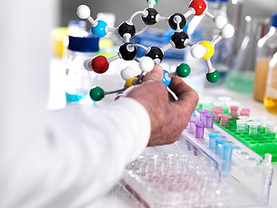Cropped hand of scientist holding molecular structure in laboratory - p1166m2001381 by Cavan Images