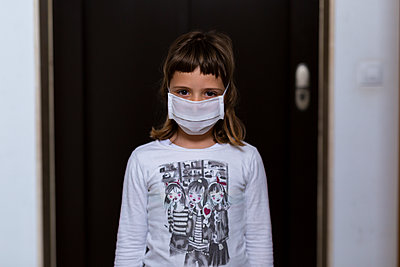 Mother putting medical mask on her daughter to protect himself from the coronavirus - p1166m2182927 by Cavan Images