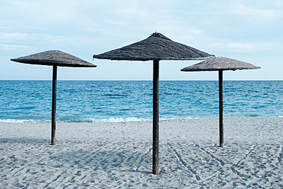 Lonely parasols on a lonely beach - p1423m2210721 by JUAN MOYANO
