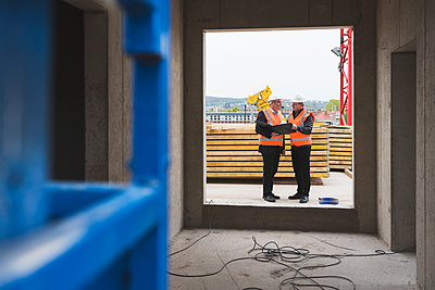 Two men wearing safety vests talking in building under construction - p300m1459872 by Daniel Ingold
