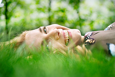 Cheerful young woman lying on grass, relaxing - p300m2083918 von Peter Scholl