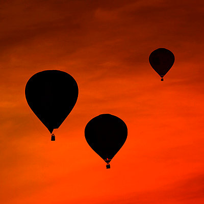 Silhouettes of three air balloons in front of red evening sky - p300m981498f by Fotomaschinist