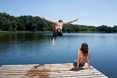 Guy dives into lake with arms outstretched as girl watches on jetty - p30119568f by Carl Smith
