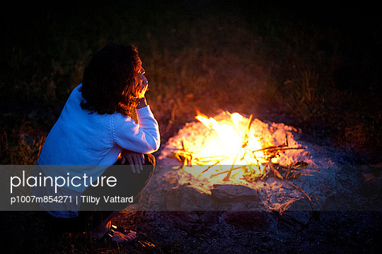 Woman sitting around a fire - p1007m854271 by Tilby Vattard