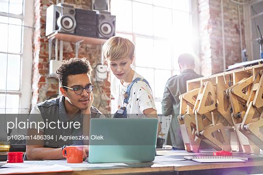 Serious, focused designers working at laptop in workshop - p1023m1486394 by Agnieszka Olek