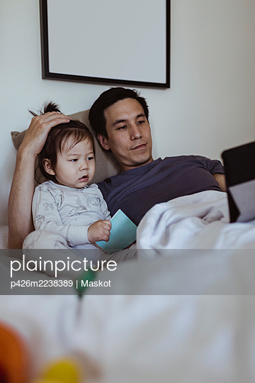 Father using digital tablet by male toddler in bedroom - p426m2238389 by Maskot