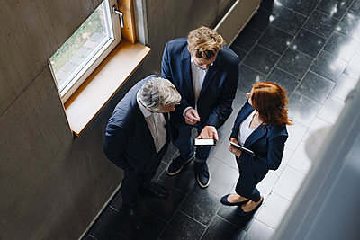 Business people with smartphone talking in modern office building - p300m2156342 von Joseffson