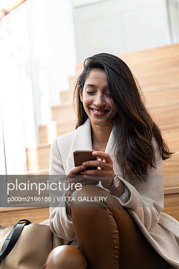 Smiling young woman sitting on stairs using smartphone - p300m2166186 by VITTA GALLERY