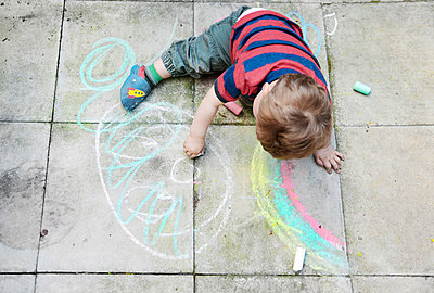 Boy drawing on garden patio tiles - p1072m836380 by Neville Mountford-Hoare