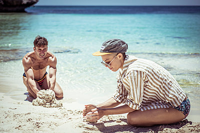young man and woman build sand castles on pristine blue beach in sun - p1166m2136690 by Cavan Images