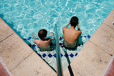 Two boys sitting in a pool - p1262m1444780 by Maryanne Gobble