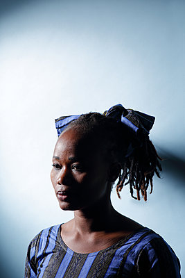 Portrait of a black woman on a blue background - p1540m2100944 by Marie Tercafs