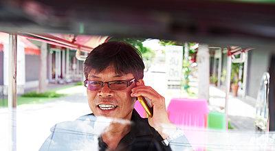Thailand, Bangkok, tuk tuk driver talking on cell phone - p300m1536093 by Ivan Gener Garcia