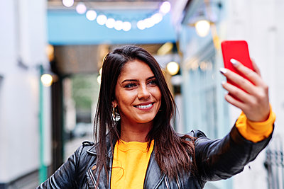 Beautiful woman smiling while taking selfie on mobile phone in city - p300m2273661 by Angel Santana Garcia