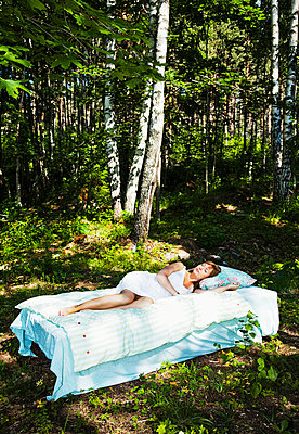 Girl sleeping in the woods - p4265620f by Tuomas Marttila