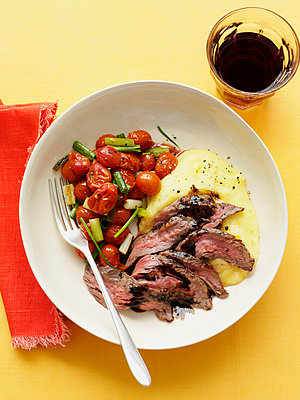 Bowl of beef with polenta and tomatoes - p429m756404 by Brett Stevens
