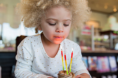 Mixed race girl blowing candles on cupcake - p555m1419546 by Inti St Clair photography